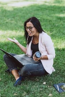ノートパソコンを使用して夏の芝生公園に座っているビジネス女性。