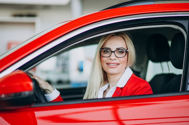 Business woman sitting in a new car in a car showroom