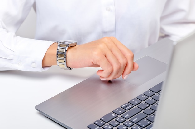 Business woman sitting in office using laptop computer looking at watch