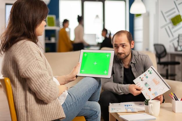 다양한 팀이 백그라운드에서 작업하는 동안 녹색 화면이 있는 태블릿을 들고 재무 통계를 분석하는 소파에 앉아 있는 비즈니스 여성
