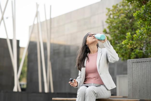 커피를 마시는 거리에 앉아 비즈니스 우먼