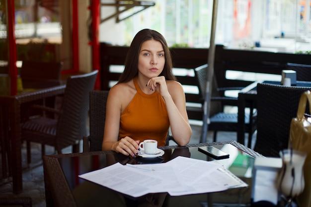 カフェでお茶の上に座っている女性実業家。重要なドキュメントの署名。ビジネスミーティング。