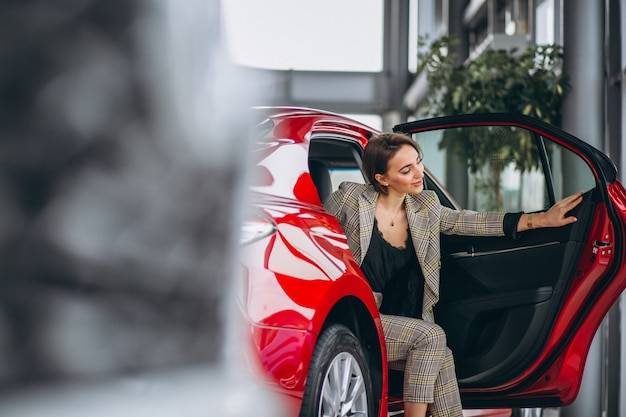 Business woman sitting in a red car