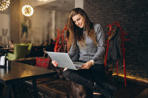 Business woman sitting on a sofa with laptop in a cafe