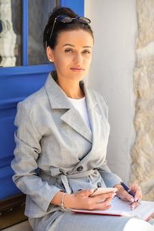 ドアに携帯電話で座っているビジネス女性