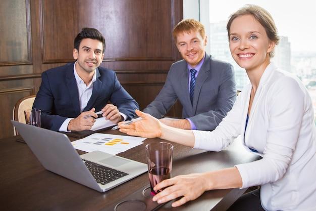 Business donna seduta con due uomini in tuta sorridente