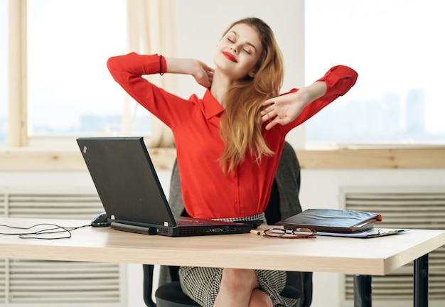 Business woman sitting at work table in front of laptop secretary
