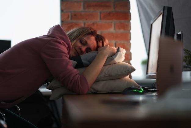 Деловая женщина, спать на подушках за столом в офисе. оставьте работу на потом