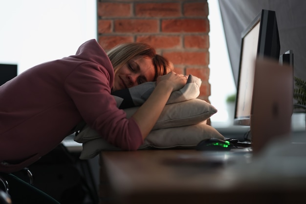 Business woman sleeping on pillows at table in office. leave work for later concept