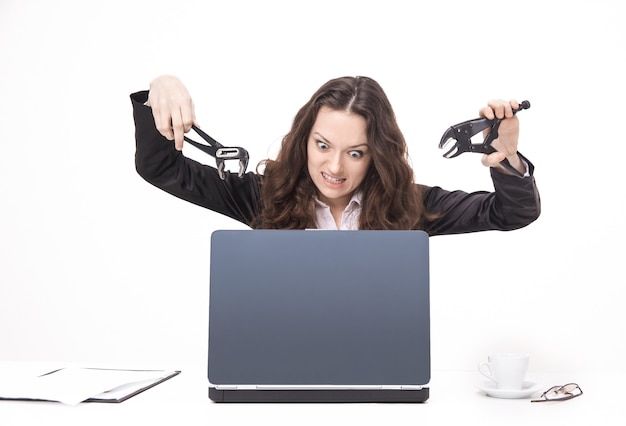 ノートパソコンを壊すビジネスウーマン。コピースペースでwhite.photoに分離されました。