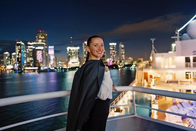 Улыбка бизнес-леди на борту корабля ночью в майами, сша. чувственная женщина в пиджаке на горизонте города. мода, красота, взгляд. путешествие по делам. страсть к путешествиям, приключениям, открытиям, путешествиям.