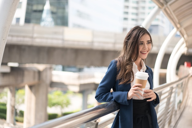 Business woman smiling beautiful holding a cup of coffee