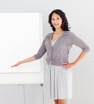 Business woman smiling and pointing at presentation board