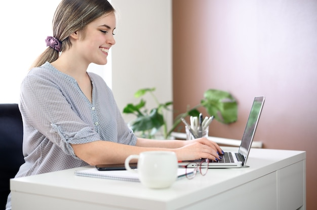 Business woman smiling, using computer at home, office. high quality photo