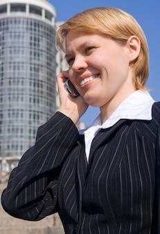 Деловая женщина разговаривает по телефону на улице