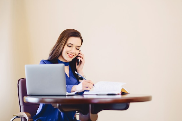 Business woman speaks by phone in office and working on laptop