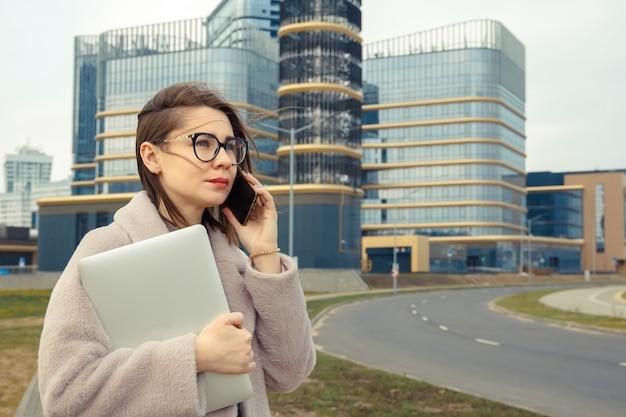 ビジネスウーマンは、近代的な企業の建物の背景に電話で話します。