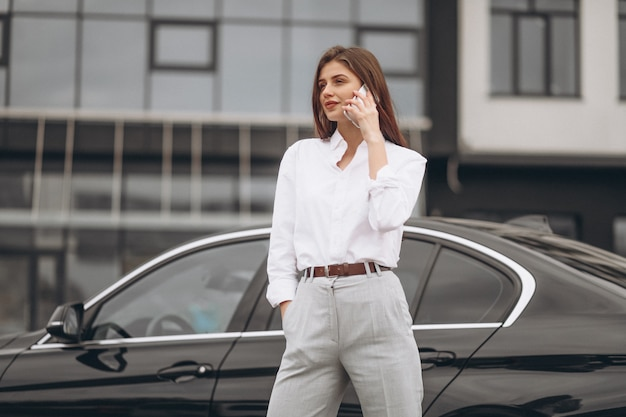 Business woman standing by the car and using phone