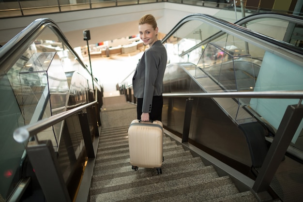 Business woman standing on escalator with luggage