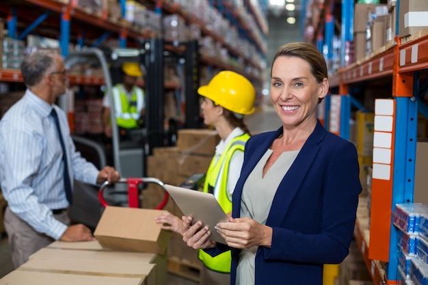 倉庫作業員の前に立っているビジネス女性