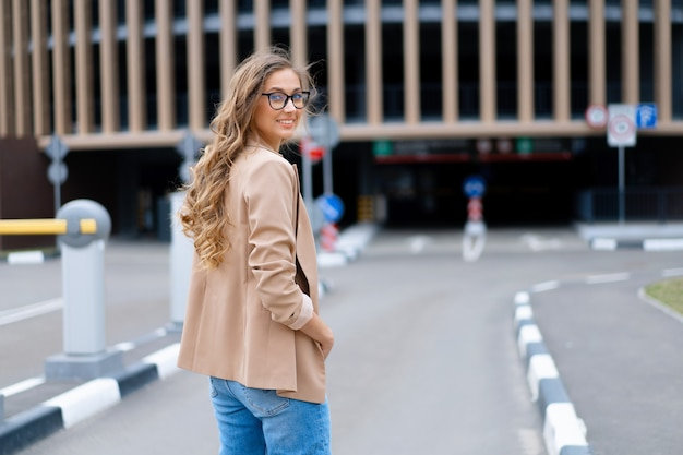 Business woman standing near indoor parking garage caucasian female middle age woman in glasses outdoors business person