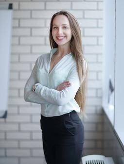 Деловая женщина, стоящая у окна в коридоре офиса.