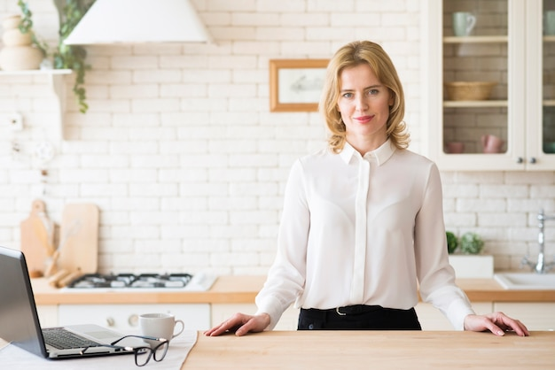 Business woman standing at table with laptop