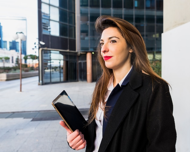 Business woman standing with tablet outside