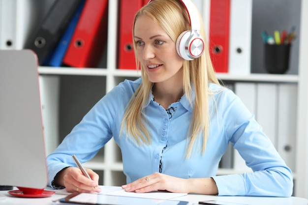 Business woman studying online. listens lecture looks at the desktop monitor. he is smiling and making notes