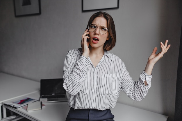 Business woman in stylish blouse emotionally talking on phone. shot of girl with glasses on background of white table with stationery.