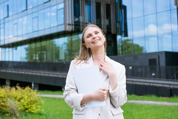 ビジネスウーマンの成功したエグゼクティブディレクターは、上に立っている薄手のジャケットで紙の文書を読みます...