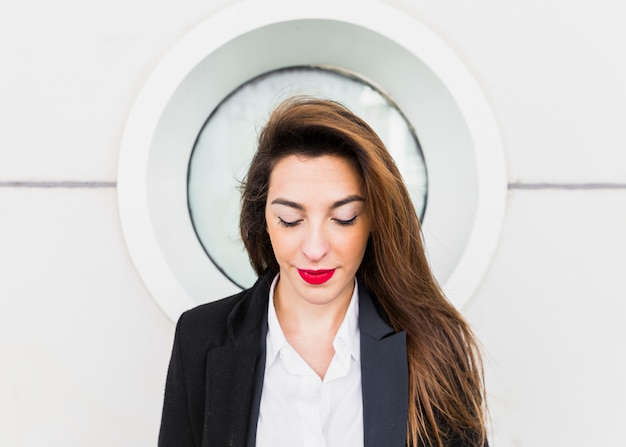 Business woman in suit on building wall background