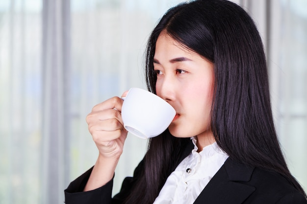 Business woman in suit drinking coffee or tea cup