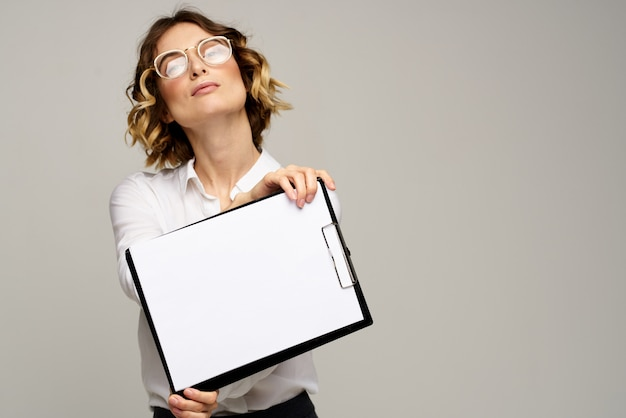 Business woman in a suit and glasses showing blank clipboard