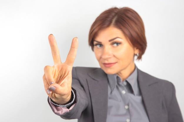 Business woman in suit shows victory sign with hand