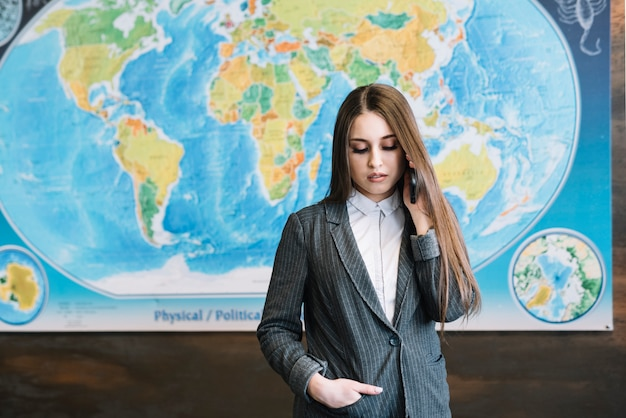 Business woman in suit talking by phone in office