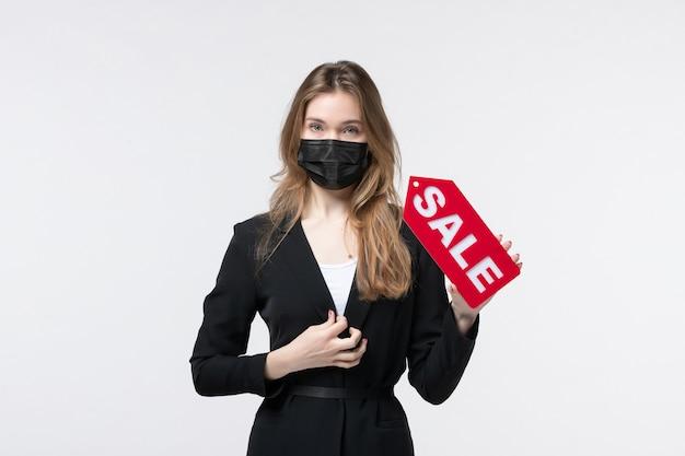 Donna d'affari in tuta che indossa la sua maschera medica e mostra la vendita in posa per la macchina fotografica su bianco
