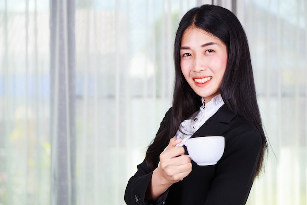 Business woman in suit with coffee or tea cup