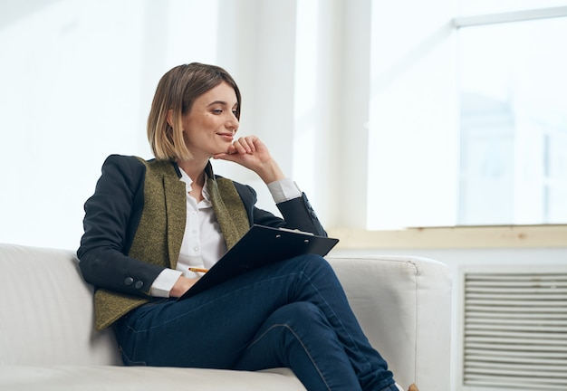 Business woman in suit with documents sitting on sofa indoors
