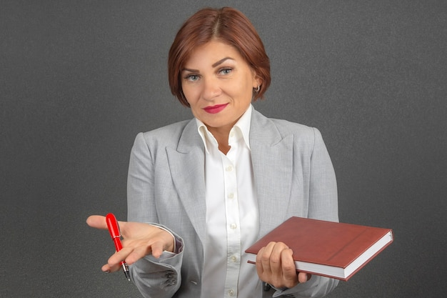 Business woman in a suit with a pen and notebook in hands