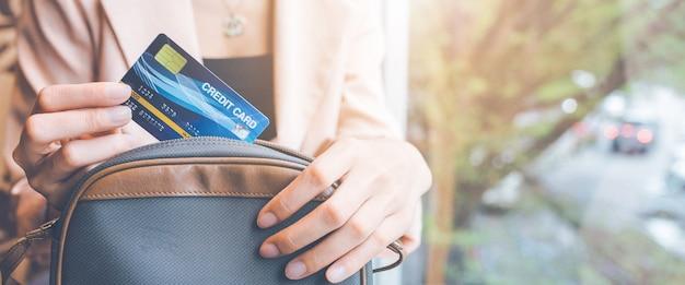비즈니스 우먼은 구매를 위해 주머니에서 신용 카드를 꺼냅니다. 프리미엄 사진