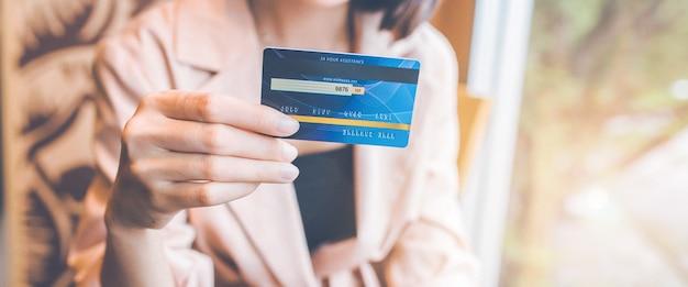비즈니스 우먼은 구매를 위해 주머니에서 신용 카드를 꺼냅니다.