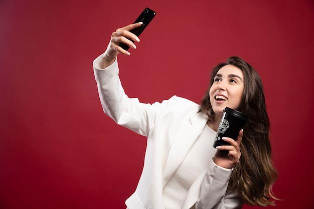 Donna d'affari che cattura un selfie con una tazza di caffè