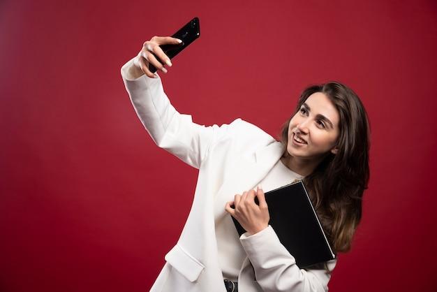 Donna d'affari che cattura un selfie con un notebook