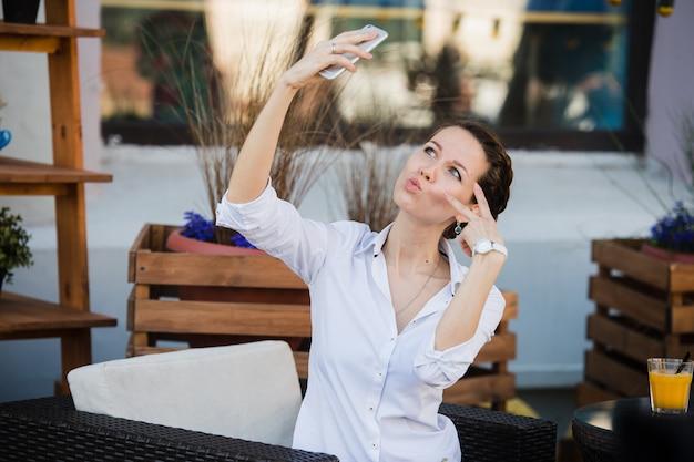 彼女の食事を待っている間昼食時に屋外カフェでオレンジのフレッシュジュースとselfieを取ってビジネス女性