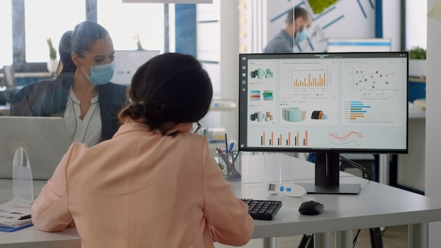 チームがコロナウイルスの封鎖中に会社のオフィスでバックグラウンドで働いている間、パートナーと電話で話しているビジネスウーマン。ウイルス病を回避するために社会的距離を保つ同僚