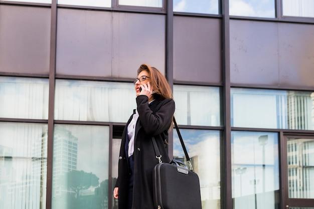 ビジネスの女性が建物の背景に電話で話しています。
