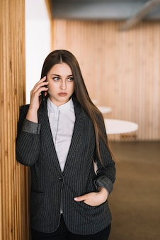 Business woman talking by phone at wall