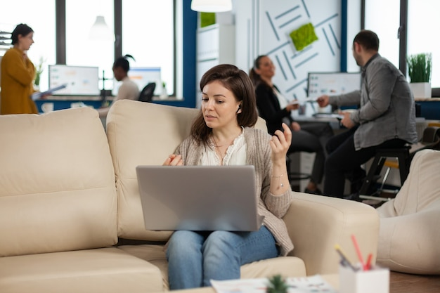Business woman talking during video conference calling from laptop sitting on couch