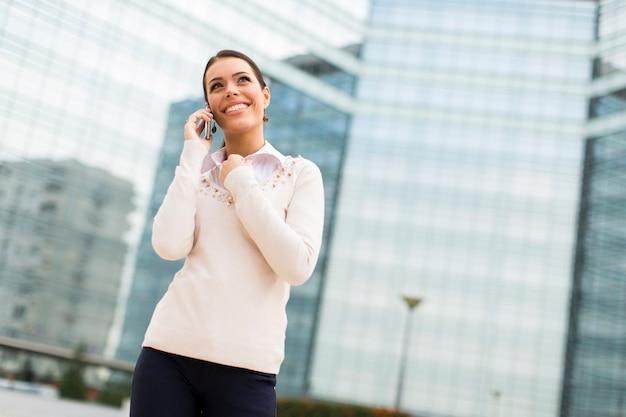 Деловая женщина разговаривает по мобильному телефону перед офисом